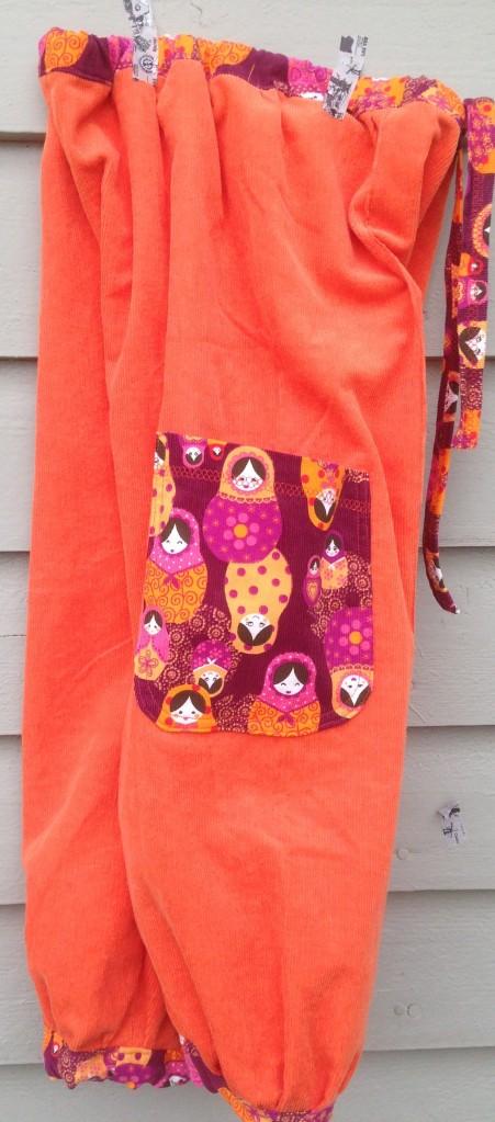 Orange bukse, sidelomme, detalj.