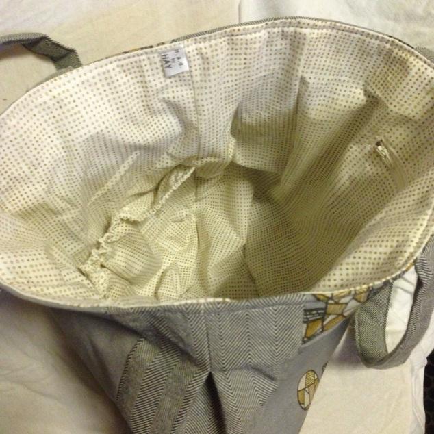 Innvendig, økologisk bomull, en stor lomme samt en mindre glidelåslomme.